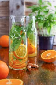 Glass water bottles filled with fruit and herbs.