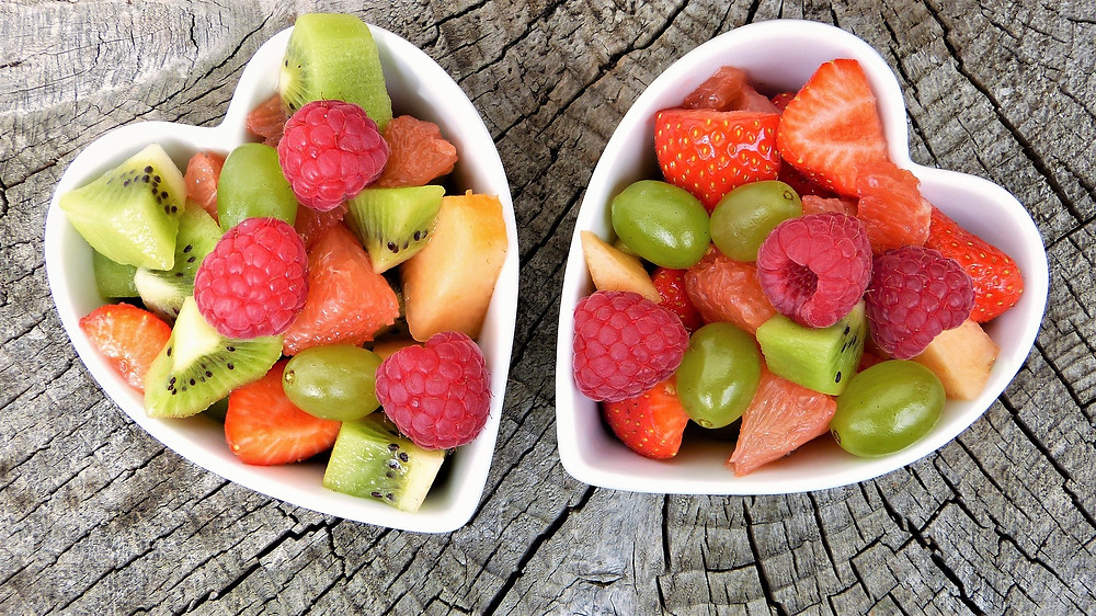 Two small heart shaped bowl with fruit salad in them.