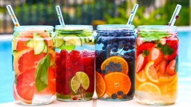 4 mason jars filled with different fruit flavored water