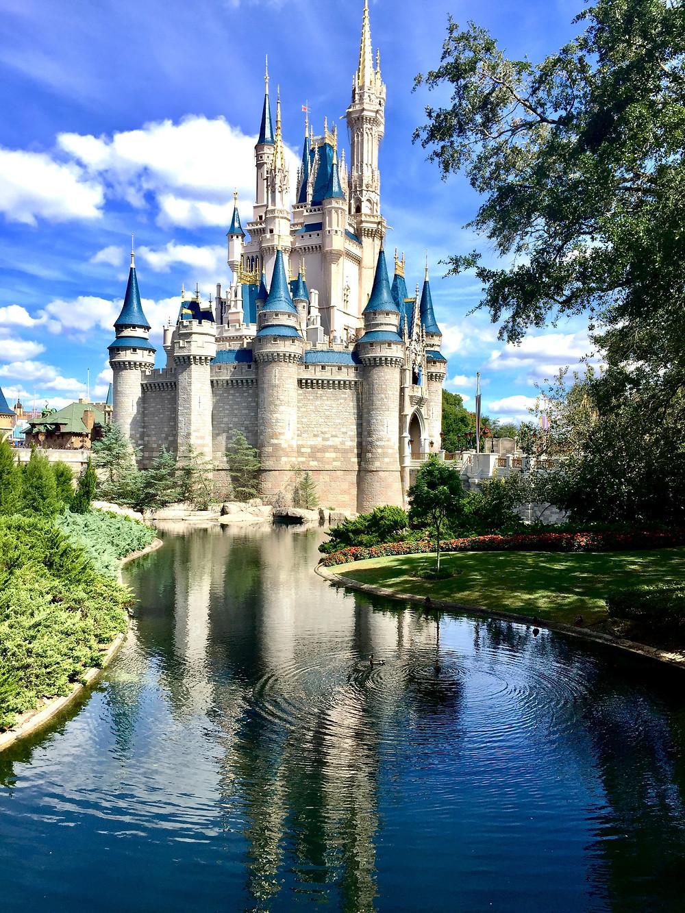 Disney princess castle behind the little river.