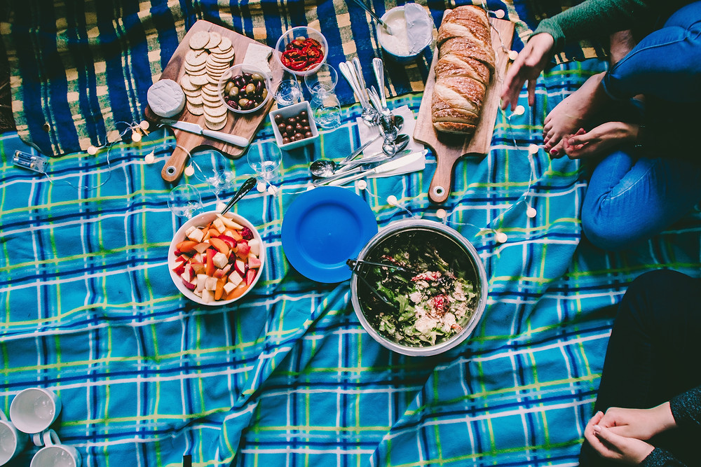Picnic blanket with cheese and cracker display, bread display, a fruit bowl, and a salad bowl.