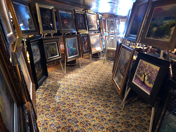 Art displayed on easels before the start of the Princess Fine Art Auction Scam