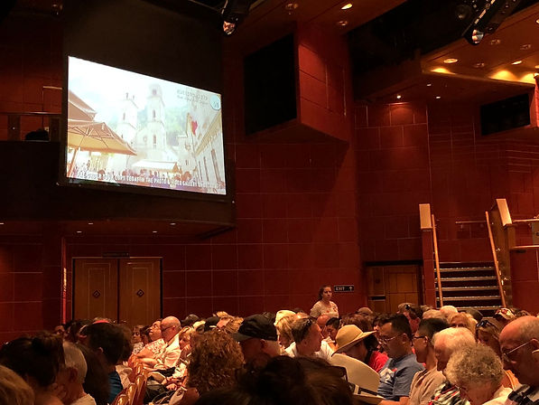 Cruisers wait in the Princess Theater until their shore excursion tour group is called