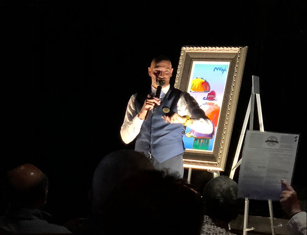 Auctioneer auctions off a Peter Max print at the Princess Fine Art Auction Scam