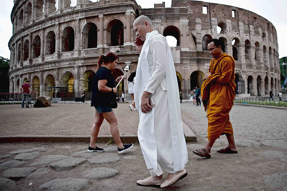 Tibetan monks, one of them engaged with his cell phone like an American business man, pass by the Colosseum
