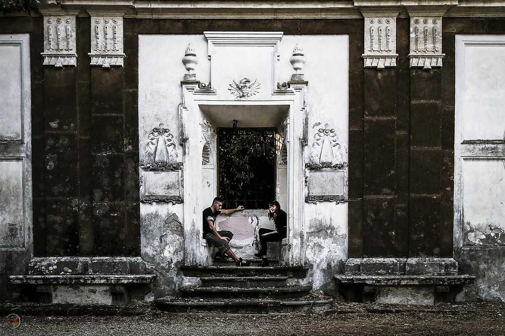 A young couple relaxes in Parco dei Daini in Rome, perfectly framed by an old door.