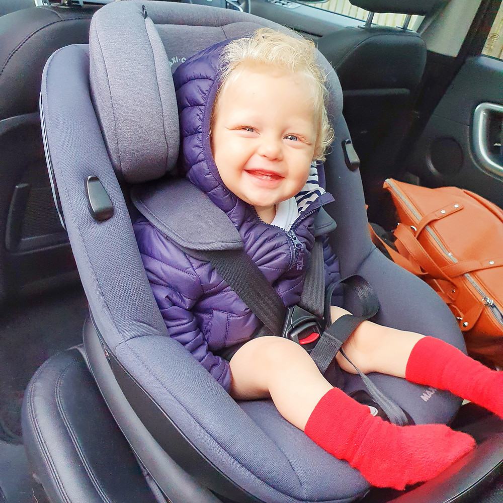 A kid with curly hair smiles from his car seat.