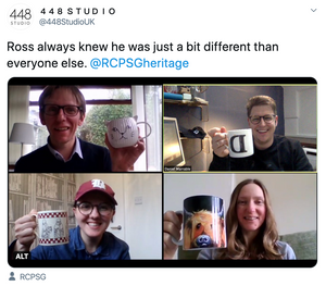 A screengrab of a vide conference call with everyone holding their coffee mug up. Ross in the top left is holding a cup shaped as a cat delicately.