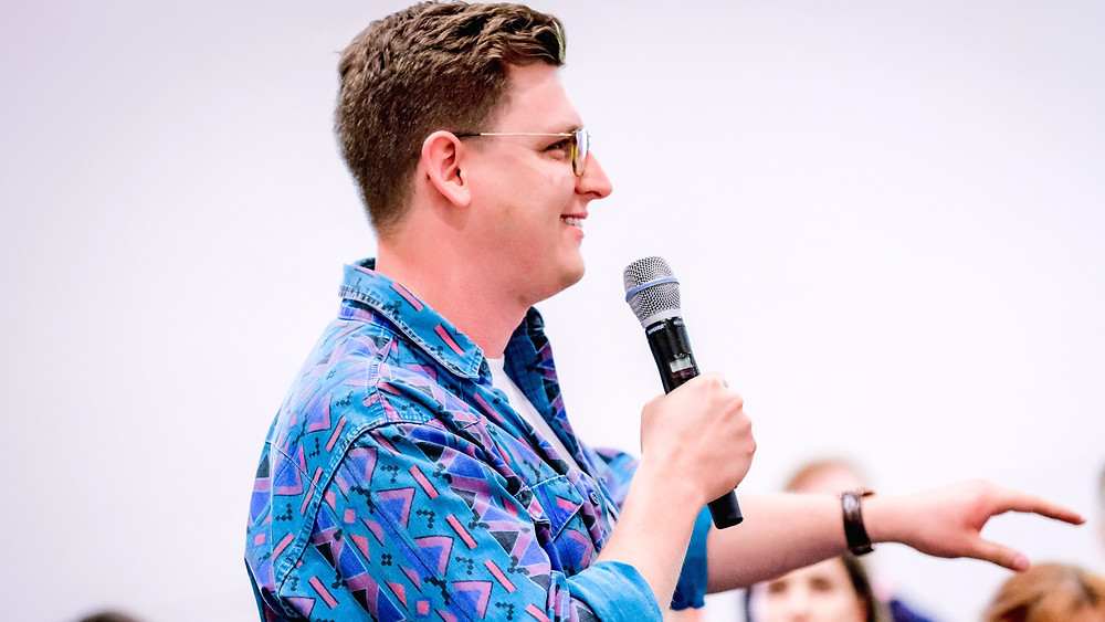 Man holding a microphone and speaking