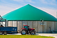 Red tractor in front of a biogas plant.j