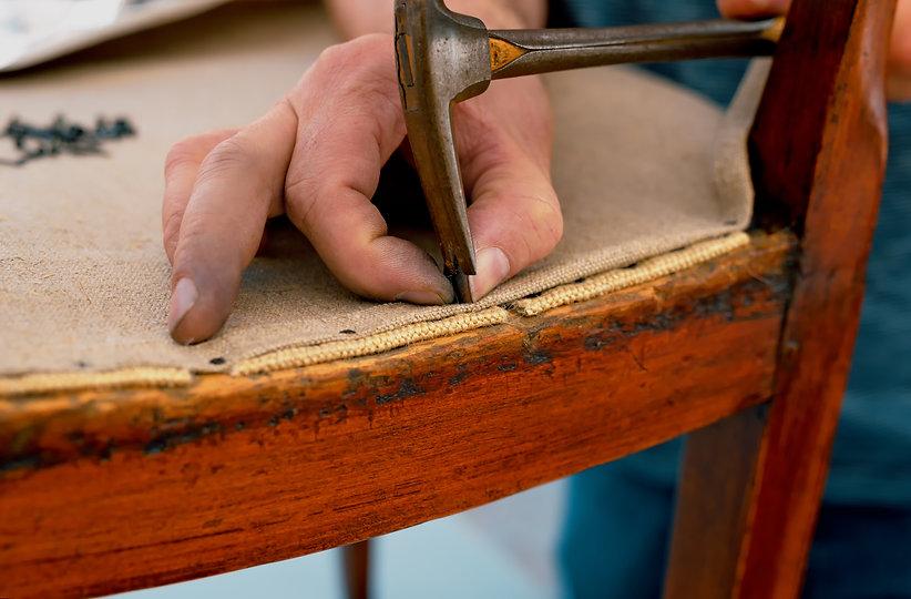 a upholsterer repairs an antique chair.j