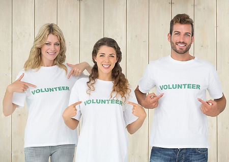 Three people wearing custom T-Shirts with Volunteer printed on them.