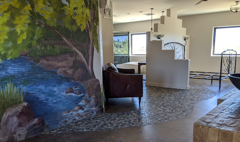 Water seems to flow from the wall mural across the floor.