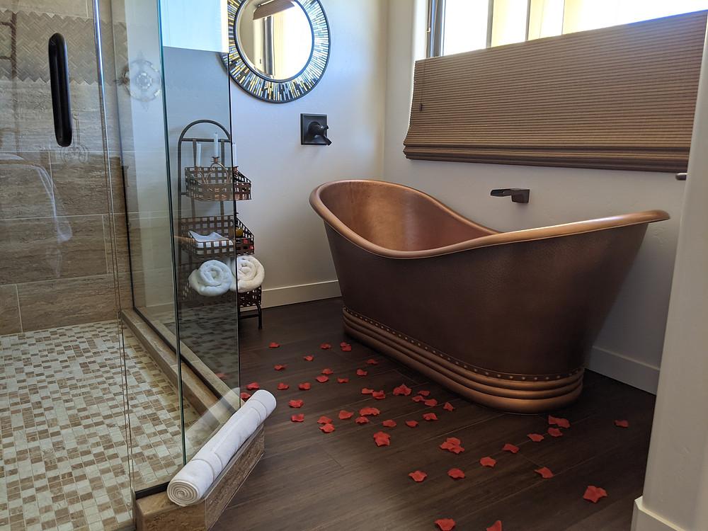 A copper slip bath tub with rose petals strewn on the floor below.