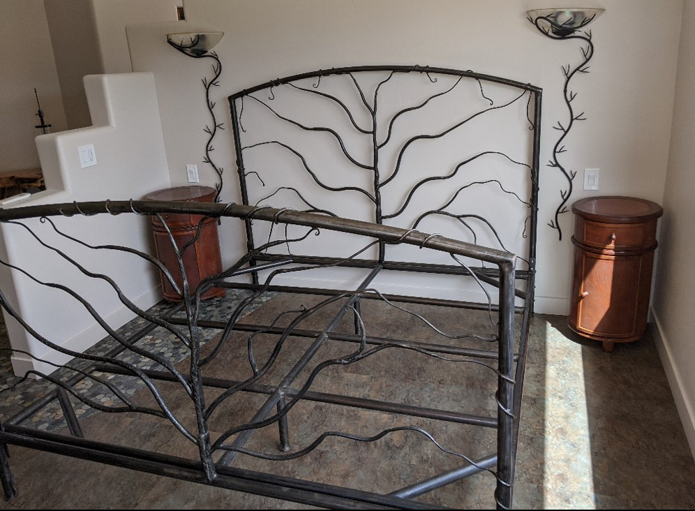 An artistic bed frame,. made of metal, appears to have vines growing on it.  Also visible are two light sconces with vines haning down, as well as two round night stands.