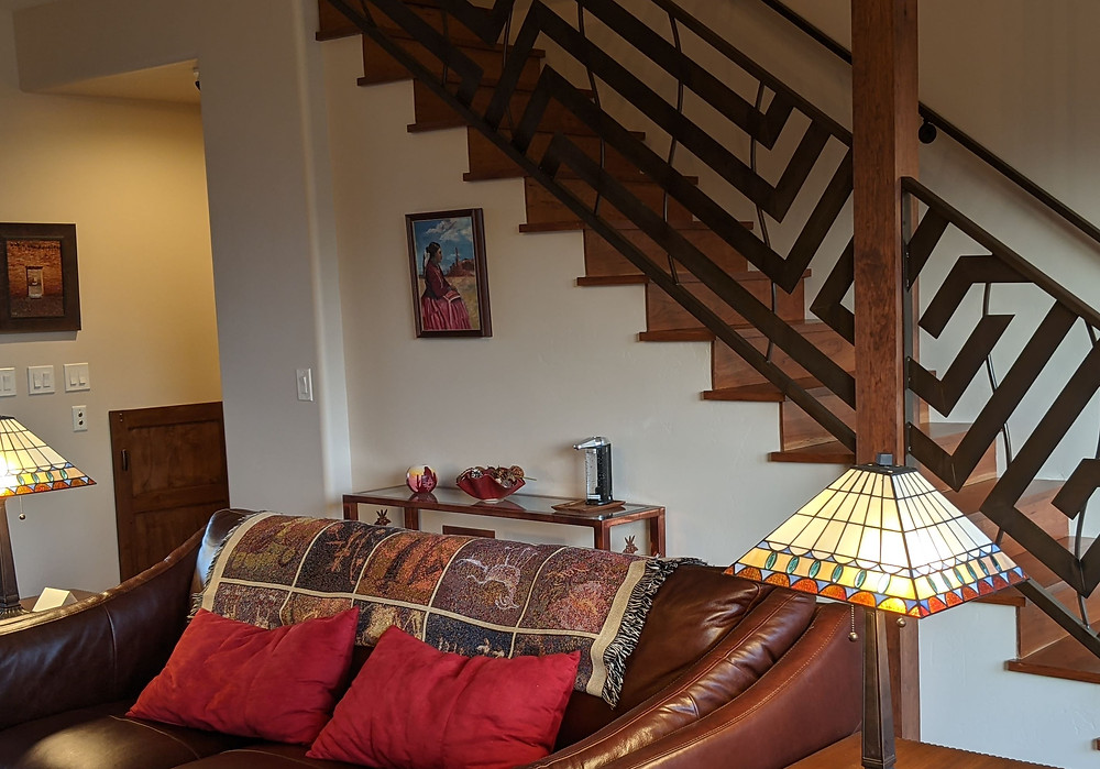 Staircase, made of wood (steps) and southwestern-styled metal (railing) leads upward, behind the Great Room couch