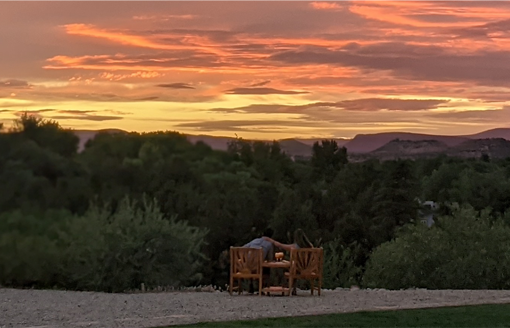 A couple sits together on comfy wood chairs at the edge of a bluff, enjoying the brilliant orange-and-yellow sky stretching far beyond.