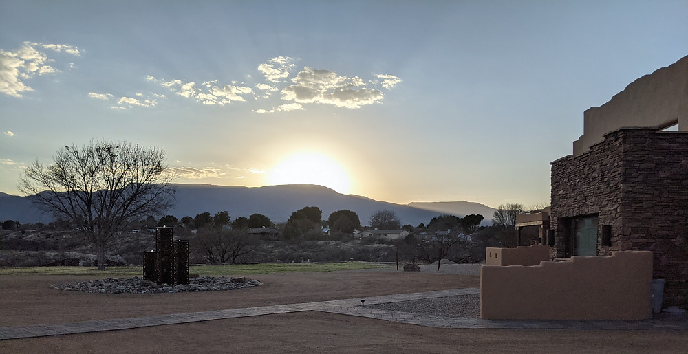 A fireball of a sunset over distant Mingus Mountain. In the foreground is the front of Origins B&B and its front fountain.