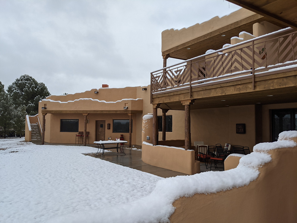 Back of the house, showing patios' railings, walls and pareapets highlighted by snow.