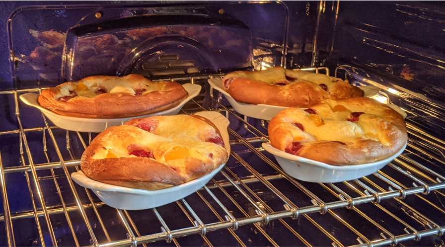Four ceramic dishes in an oven, with a souffle-like treat - dotted with raspberries and peaches - puffing up high.