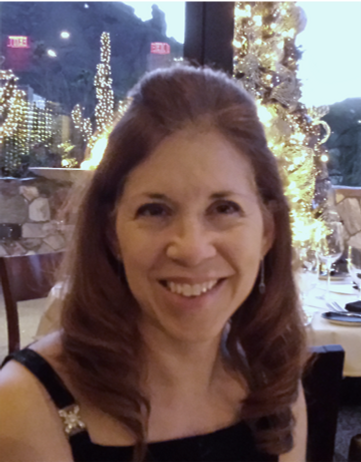 Photo of Karen in a black dress, at dinner, with holiday lights and Camelback Mtn behind her.