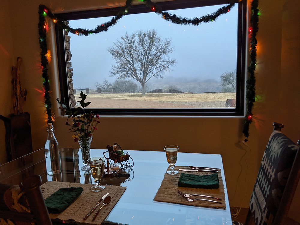 View past a set breakfast table, through a window. A tree is sikhouetted by dense fog.