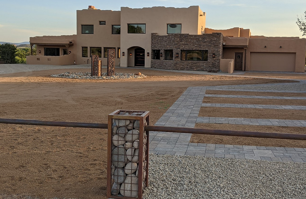 View of the front of the house at sunrise, showing parking spaces in the foreground and fountains lit by the rising sun.