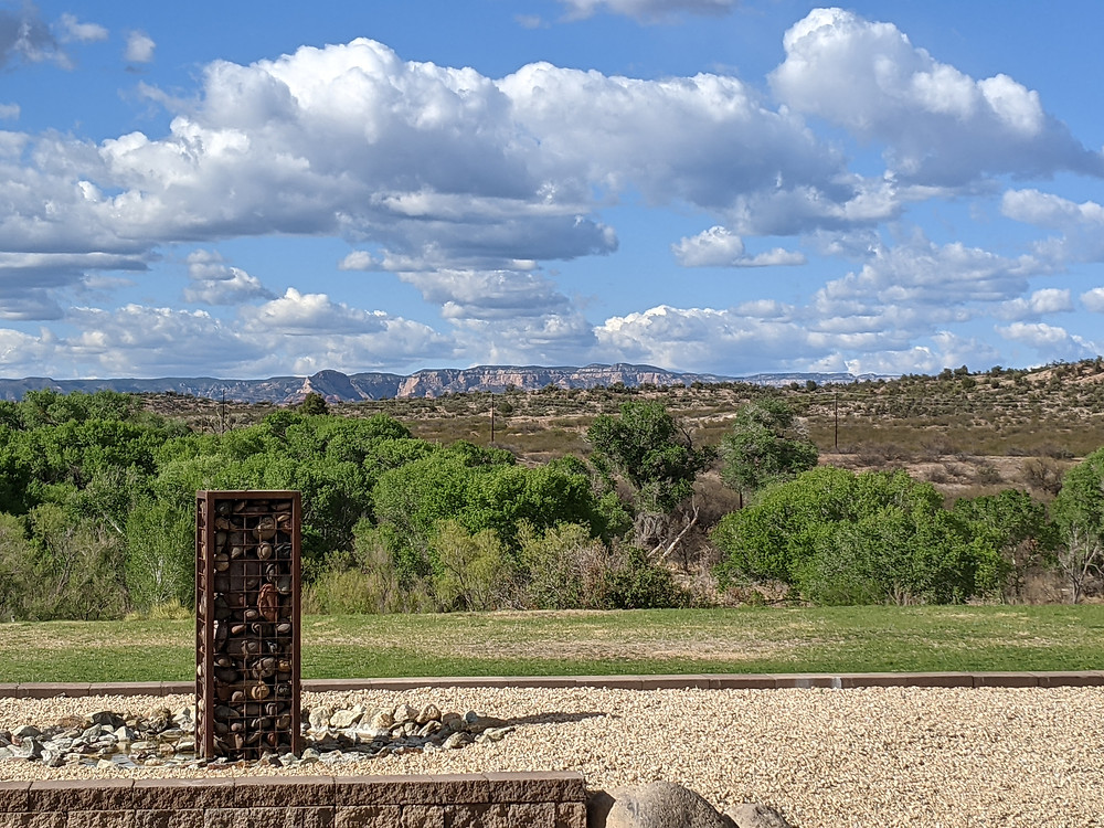 Mildly threatening clouds dominate the distant Red Rocks of Sedona. In the foreground are greening Cottonwood trees which line the Verde River.