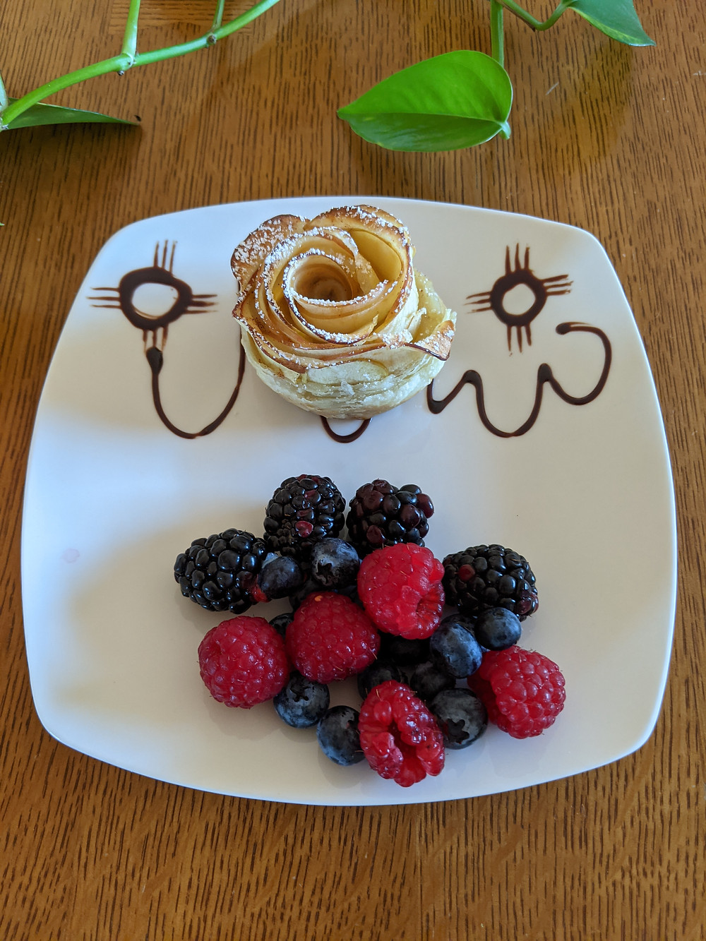 A pastry, looking like a light brown rose, sits above a small pile of blackberries, raspberries and blueberries. The plate is decorated with chocolate swirls.