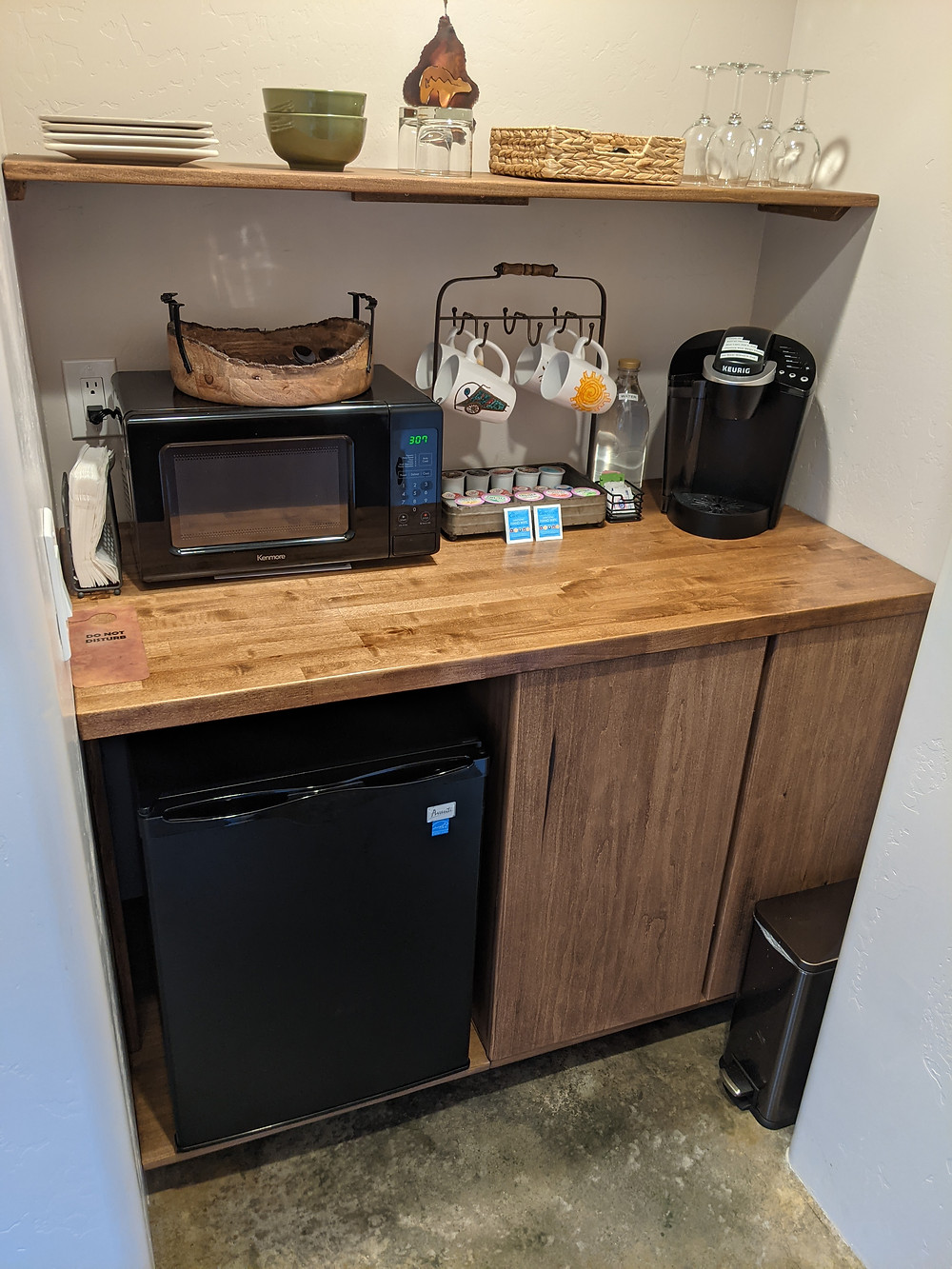 Wood cabinet holds a microwave, coffee maker and coffee mugs, with a refrigerator below. Arranged on the shelf above are plates and glasses.
