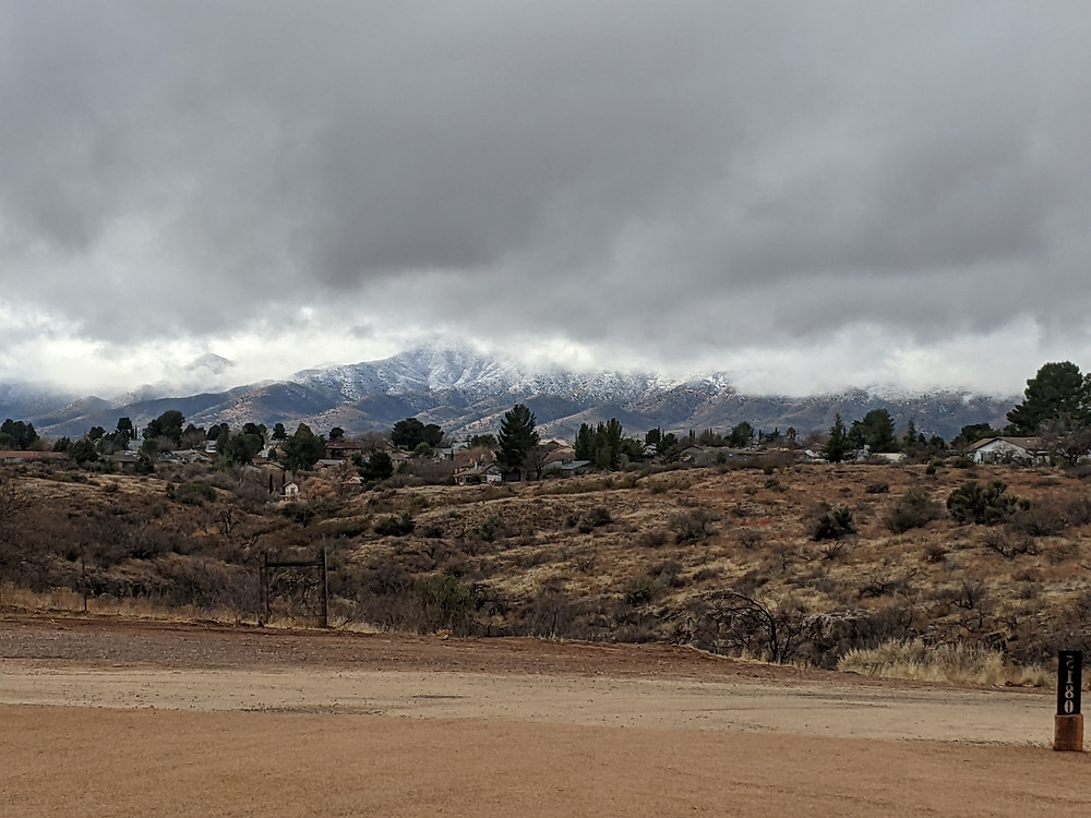 Snow-covered mountain in the distance, with dark grey clouds partly obscuring its view.