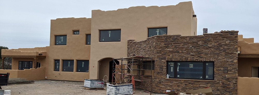 3-toned stucco house (front) and stone-clad Dining Room & Office.