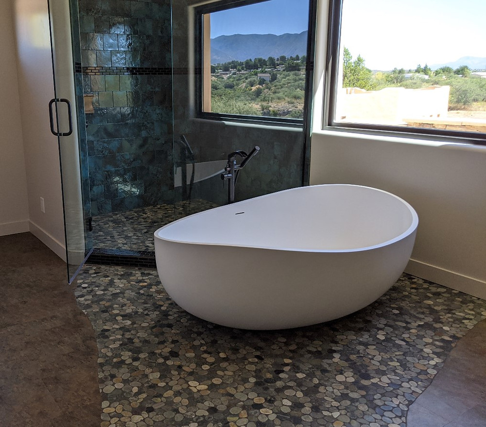 Boat-like tub appears to float in the river rock tile.  Behind is the blue-tiled shower.  Visible through the window are the Black Hills.
