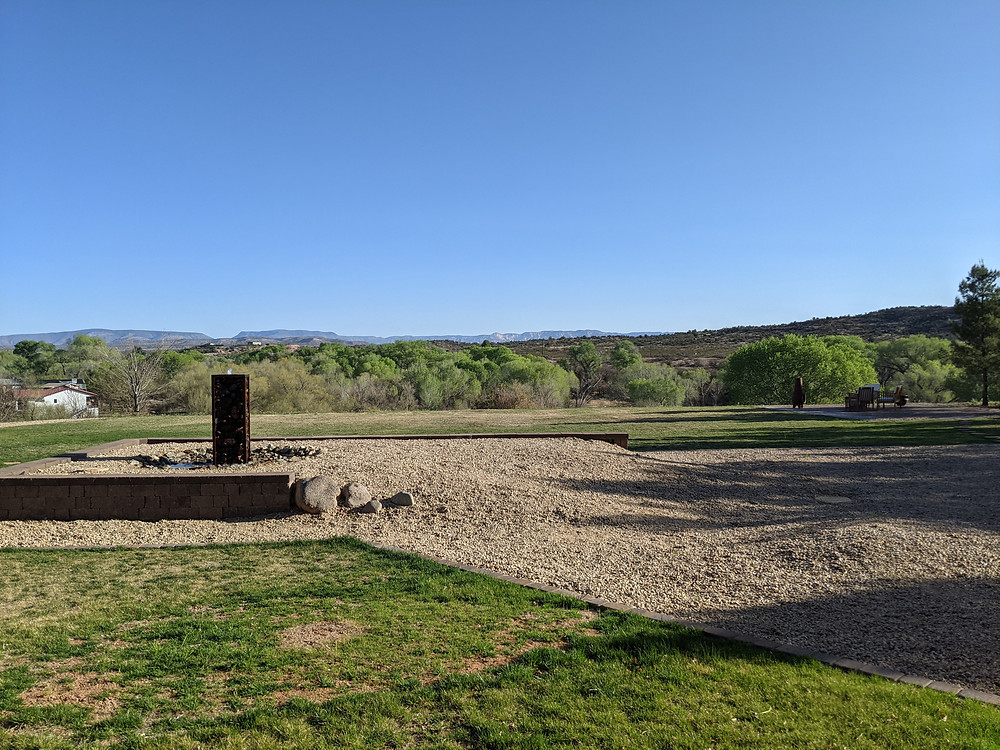 View toward the Verde River, showing much greener trees beyond the greening grass.