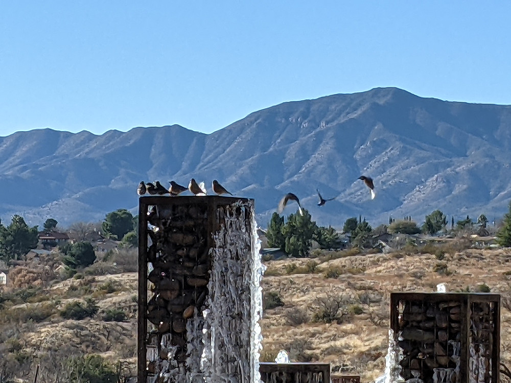 Birds sit on top of the top metal & stone fountain, with water gurgling from its top while ice clings to its side.  Three birds are mid-flight, about to join their friends.  Mountains are seen in the distance.