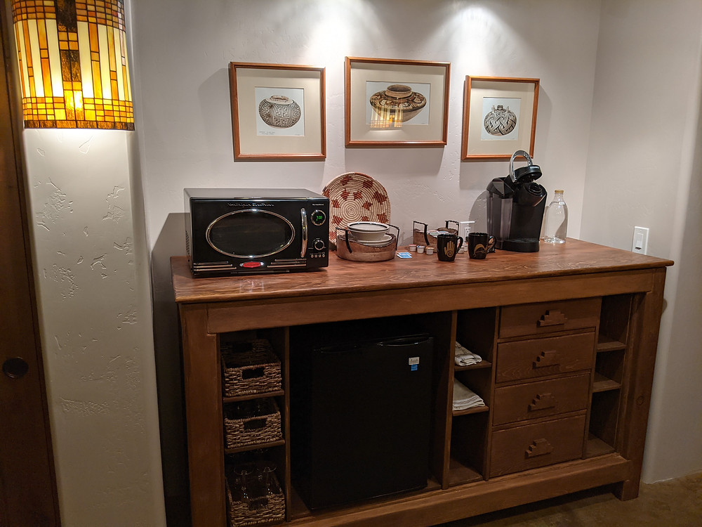 A large dark wood open cabinet holds a microwave, refrigerator, coffee maker and eating utensils.