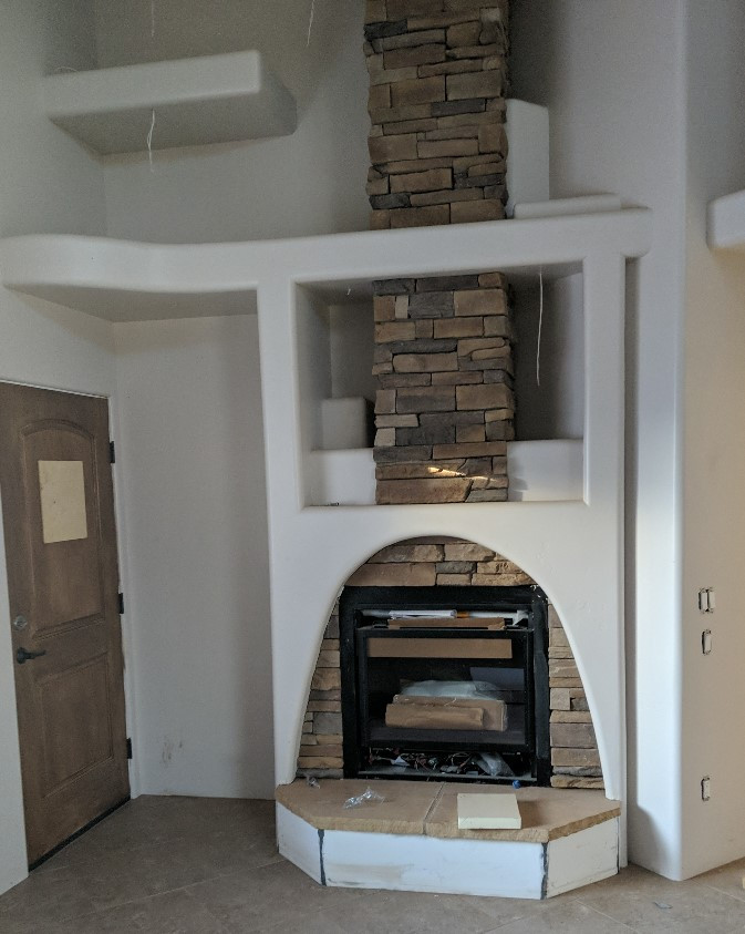 Family Room fireplace, with a front of stacked stone and featuring several nooks for showcasing pots