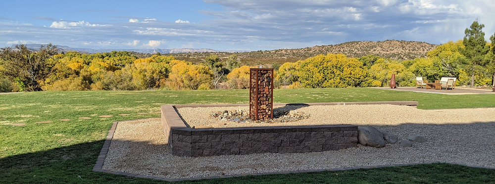 Colder weather brings a change in leaf color; view of Verde River, looking past a field of grass and a stone water fountain.