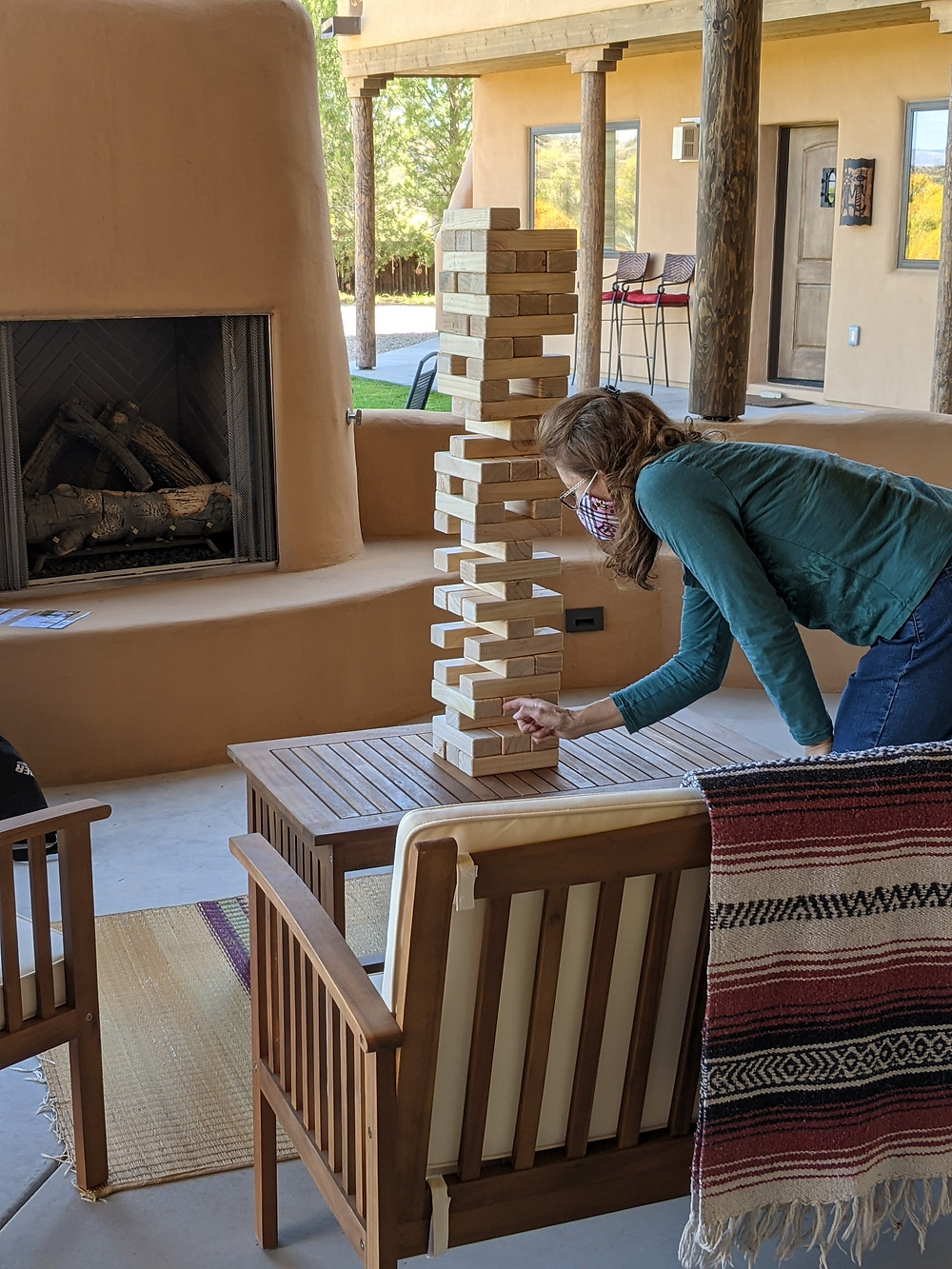 Woman playing Jenga on a patio, with fall colors reflected in the windows behind her.