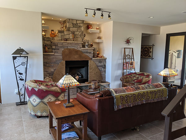Great Room, centere on a stone fireplace displaying native and modern pots and baskets.  Comfy chairs and a couch surround a glass coffee table.