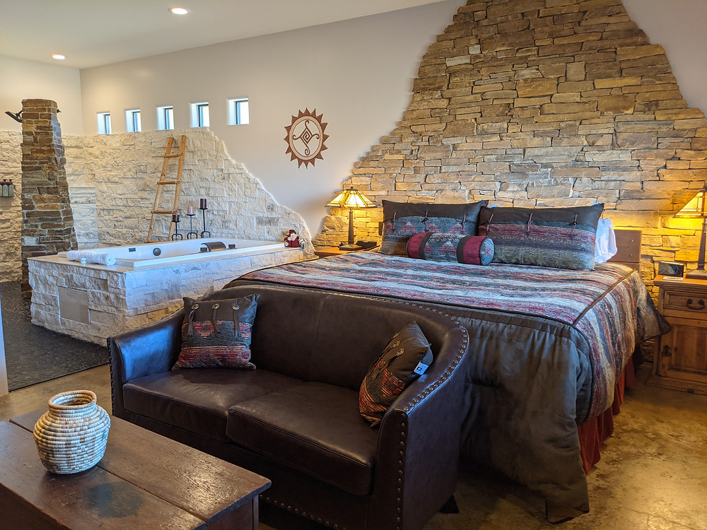 Walls of stone - brown behind the rustic bed and white behind the bath tub and brown stone shower tower, provide an aura of earthy elegance.