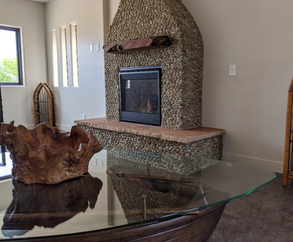 View of the fireplace, with the boat table in the foreground.