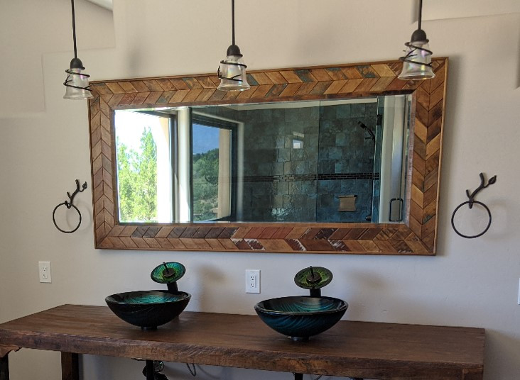Two sinks, at a wooden, chevron-lined mirror, with rustic towell rings and drop lights.  The blue-tiled shower is visible in the mirror.