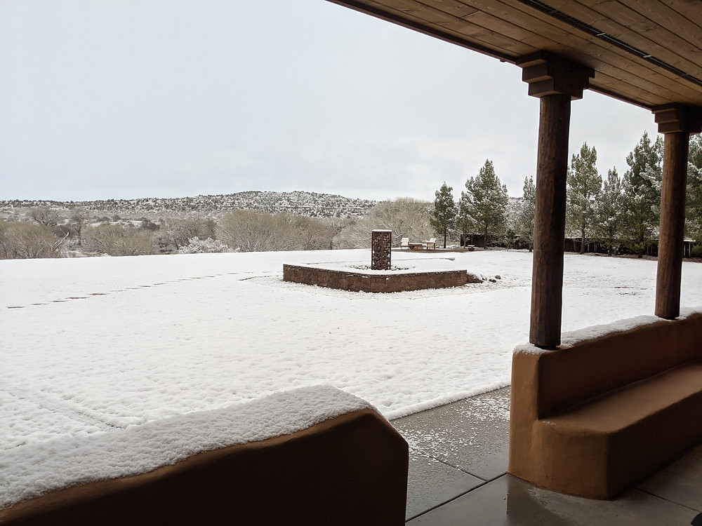 View from a covered patio, with snow-covered yard in foreground and snowy hills in the distance.