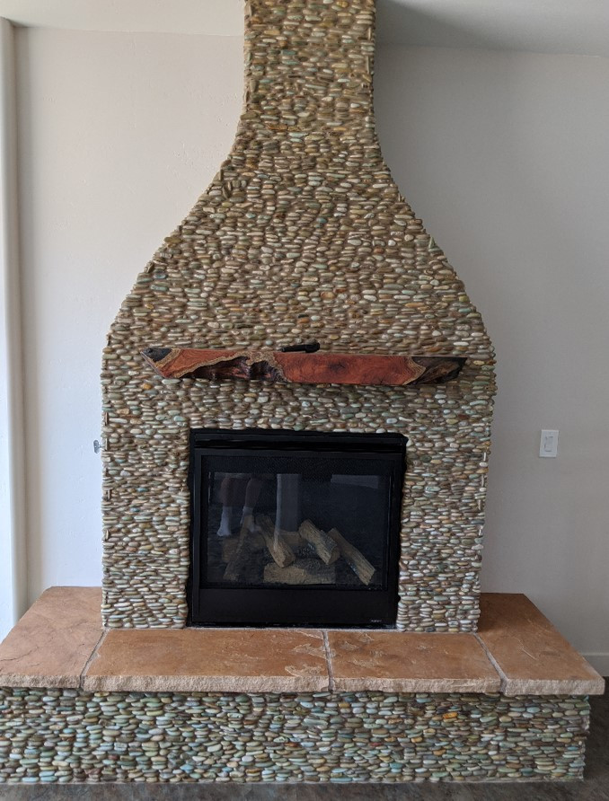 Fireplace made of small river stones grouted into place.  A simple mantel of mesquite wood hangs above the firebox.