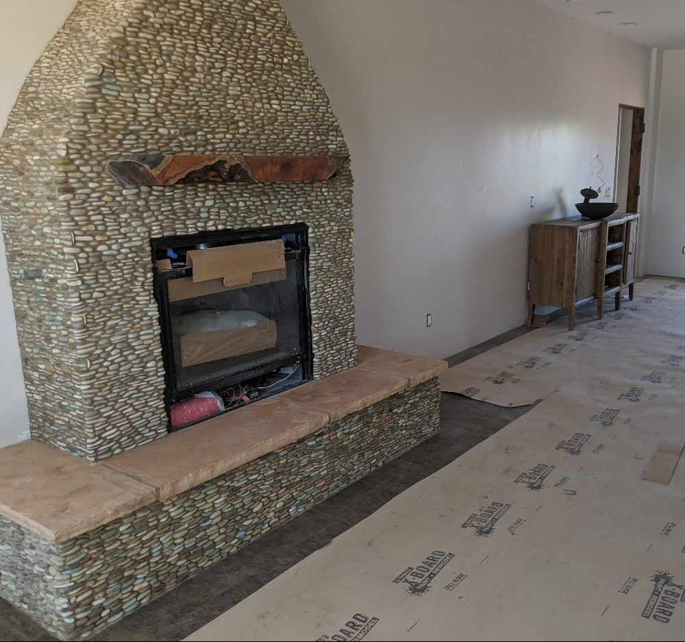 River Room fireplace, which is faced with stacked stones which look like perfect rocks for skipping across a river's surface
