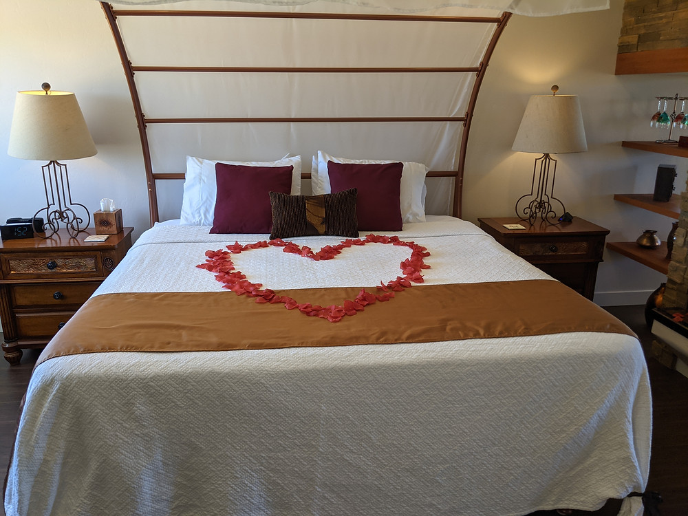 Rose petals, strewn in the shape of a heart, decorate a copper-framed bed.