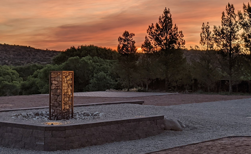 Orange sky, lit by the rising sun, appears beyond the backyard fountain and through the pine trees.