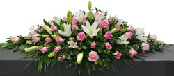 whites and pinks lillies and roses caske