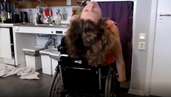 Dansare i rullstol böjer sig bakåt med stängda ögon